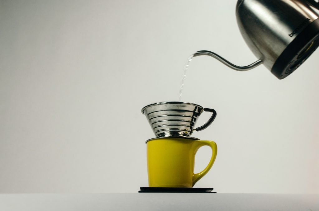 Pouring water over a Kalita dripper on a mug