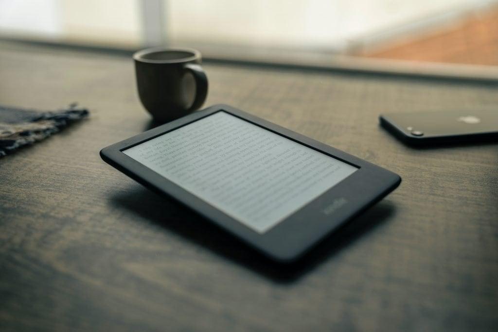 A Kindle over a table along with a mug and a phone