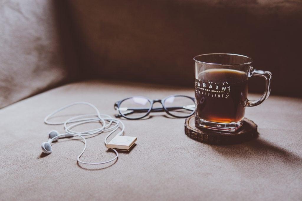 Glass Mug with black coffee, glasses, and headphones