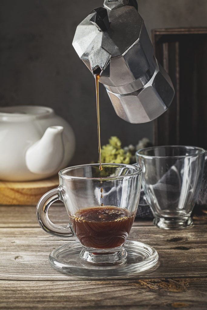 Serving coffee in a glass cup with a moka pot